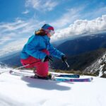 Nicole Lewis carving in the spring sunshine off the Summit at Mt Buller